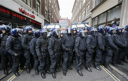 Police officers form a cordon after raiding a building used as a base for demonstrators protesting against the upcoming G8 summit in central London